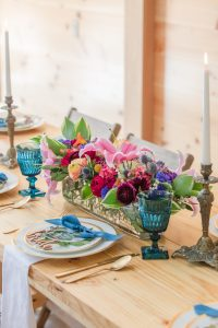 Gorgeous spring flowers and place settings on harvest tables at Events At Hemlock Springs.