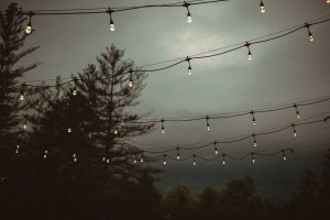 Gloomy sky above cafe lights with the forest in the background at Events At Hemlock Springs.