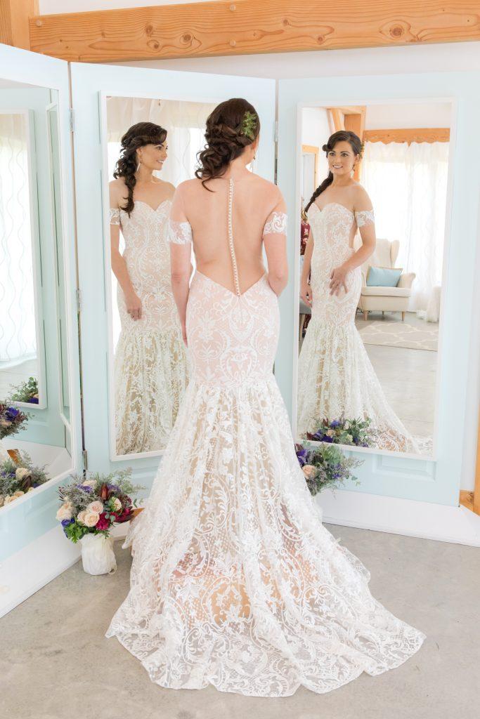 Bride in her wedding dress gazing in the mirror in the Bridal Suite at Hemlock Springs.