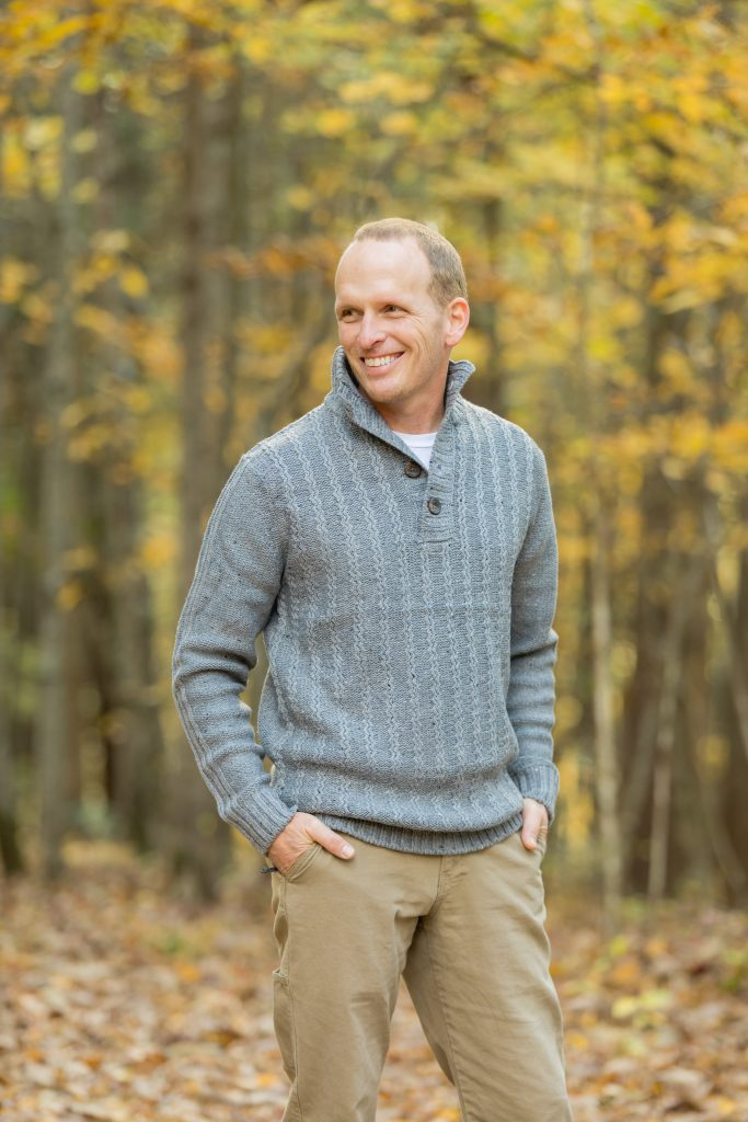 Handsome Groom smiling on his wedding day with fall foliage in the background.