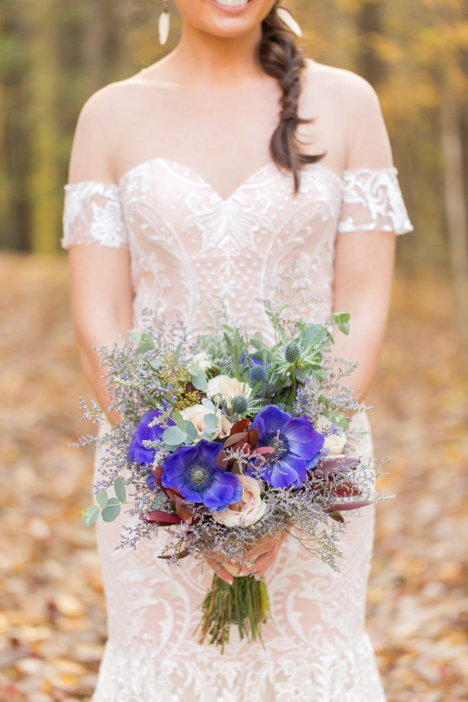 Bride in stunning wedding dress holding a bridal bouquet of flowers and herbs in the woods.