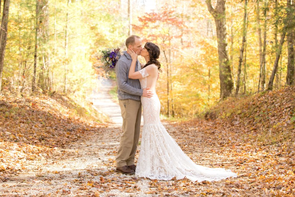 Bride and Groom kissing on a country road in the fall.