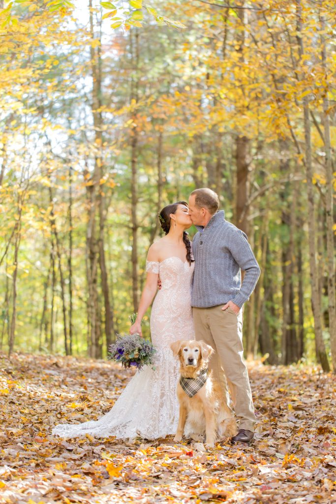 A bride and groom kiss as their golden retriever sits in front at a gorgeous fall wedding in the Red River Gorge.