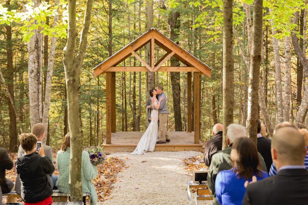 Bride and groom kiss under a gazebo in a forest wedding at Hemlock Springs.