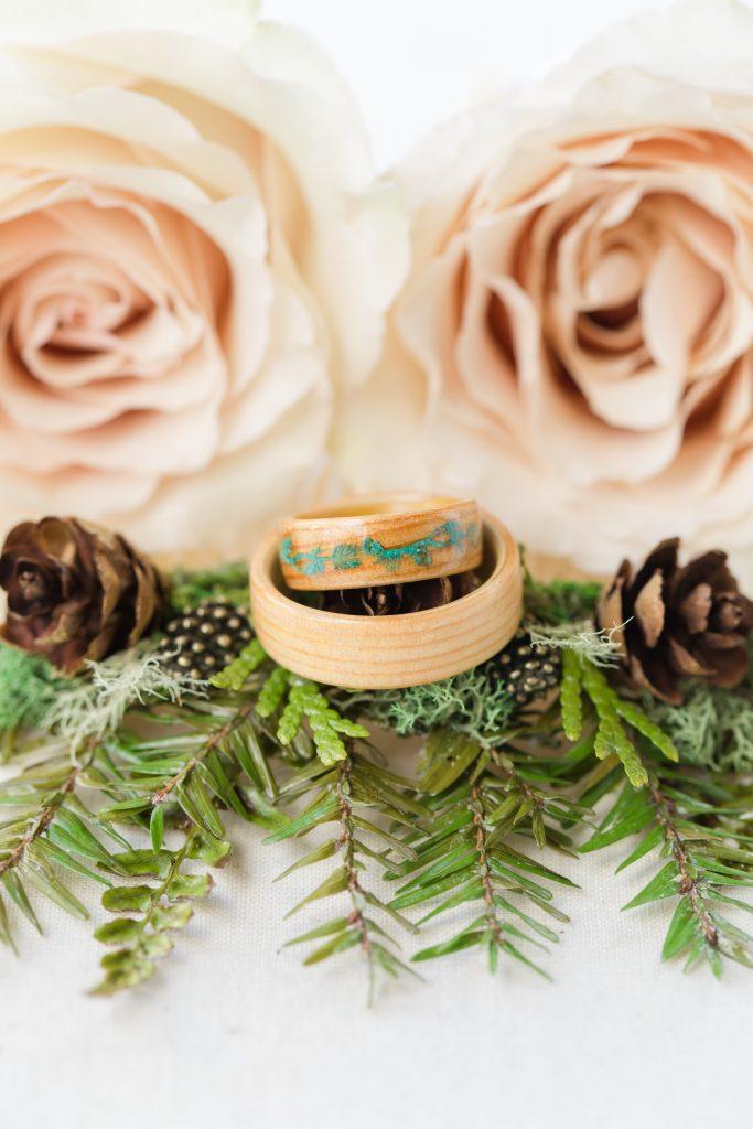 Custom made wood wedding rings sit atop hemlock greenery and roses.