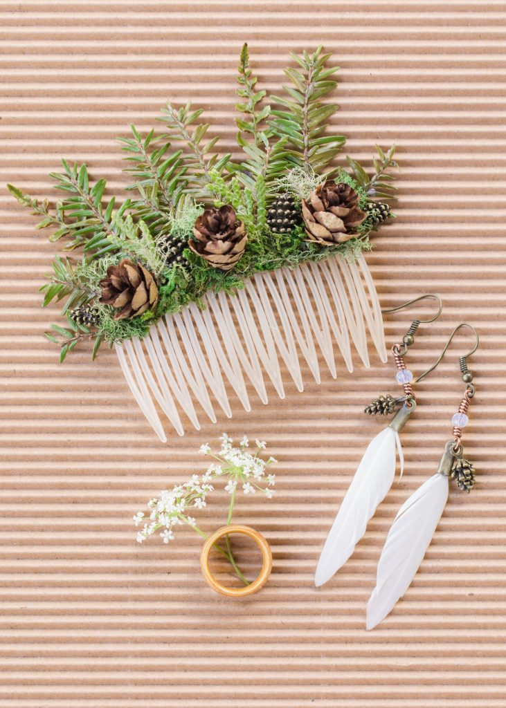 Bridal details with a woodland twist with a live greenery hair comb, wood ring and feather earrings.