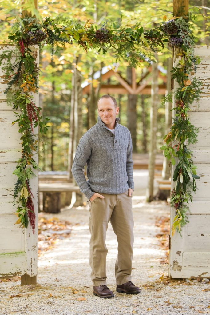 Handsome groom stands between white antique doors at a forest wedding.