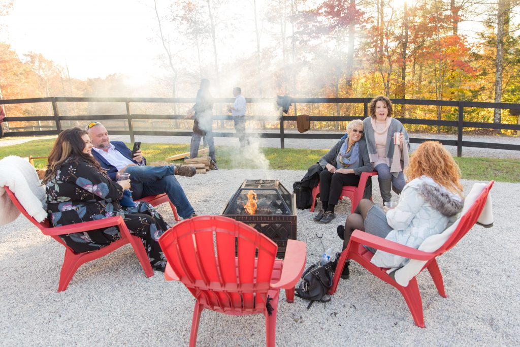 Wedding guests laugh around a fire pit at a fall wedding in the Red River Gorge.