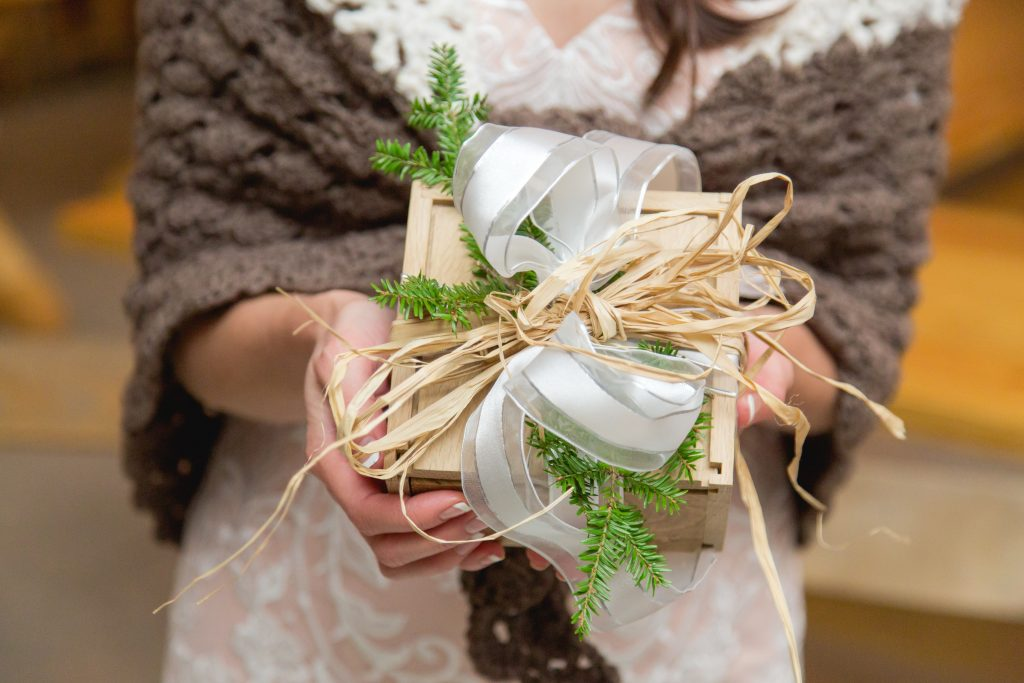 Bride holds a handmade gift box from a guest decorated with hemlock branches and twine.