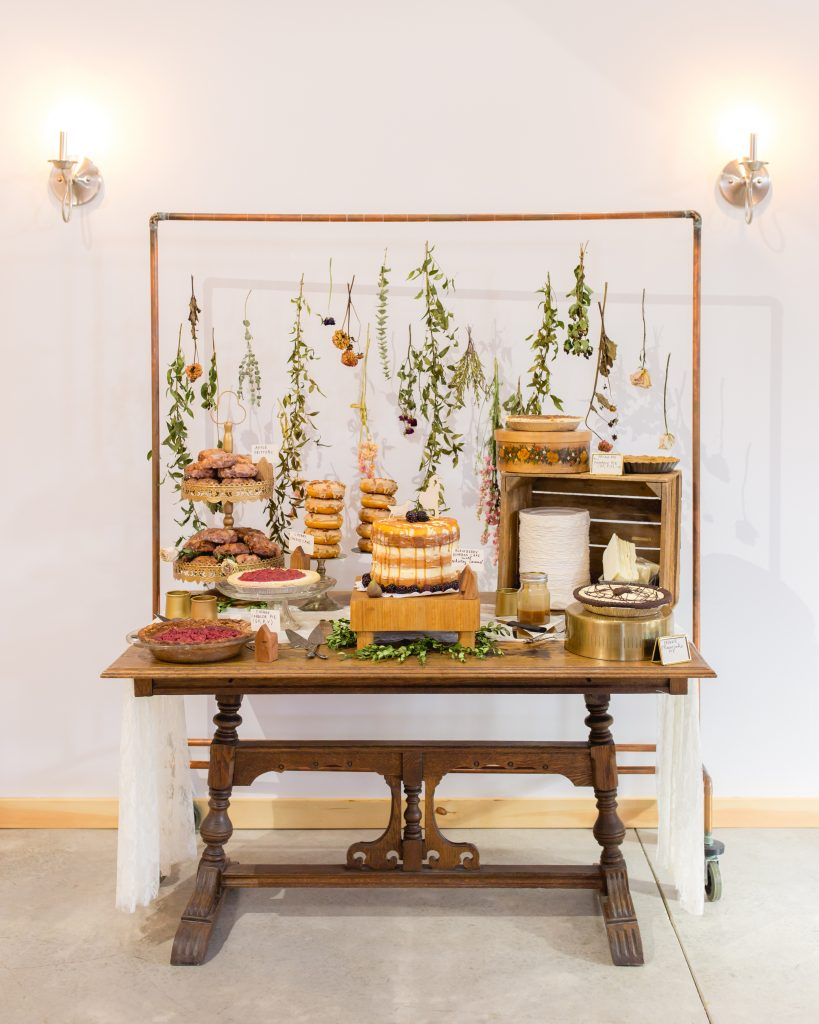 A natural and recycled dried flower and copper pipe backdrop for a wedding dessert table.