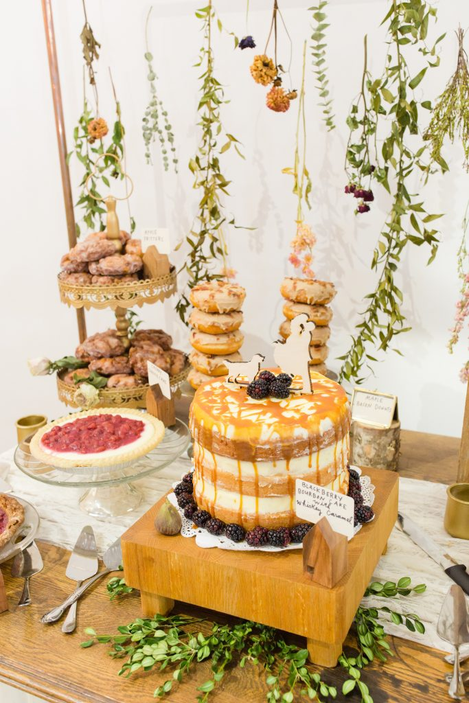 Dried flowers make a beautiful backdrop for a wedding dessert and cake table.