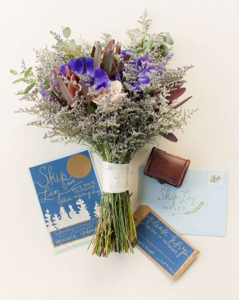 Beautiful bridal bouquet of flowers with woodland wedding invitations.
