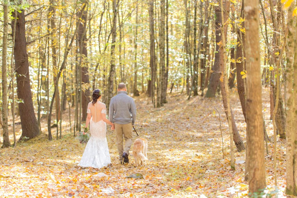 Bride and Groom walk down a wooded path in the fall with their Golden Retriever by their side.