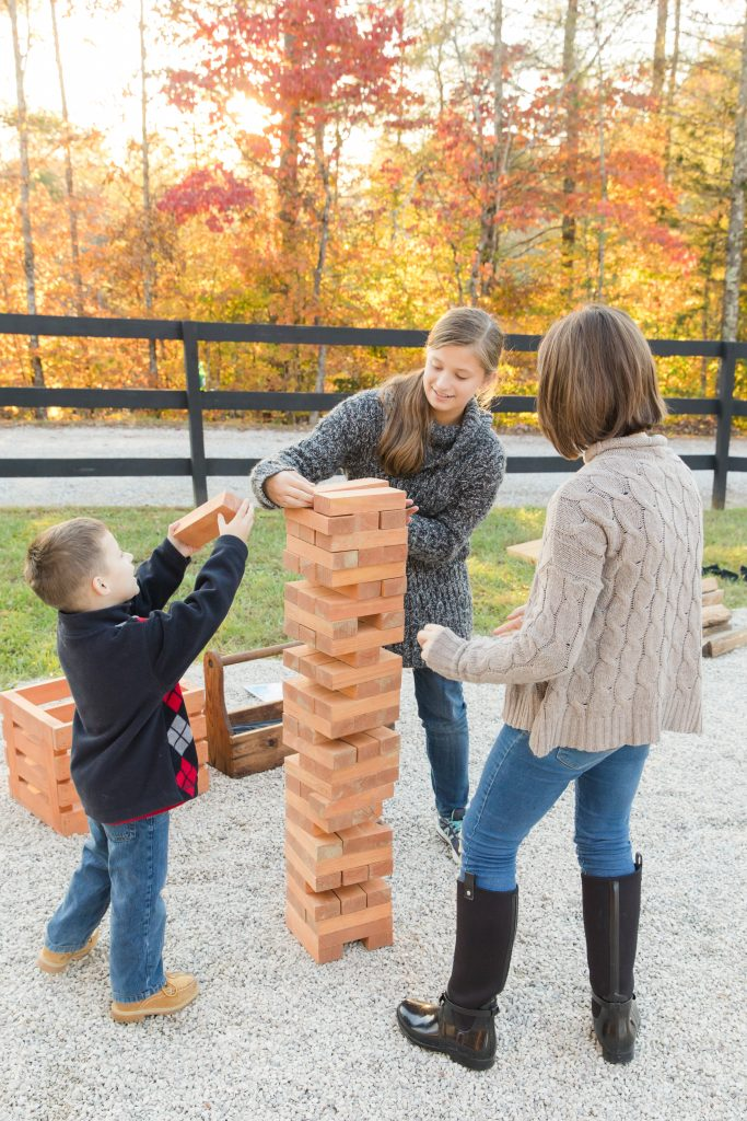 Beautiful fall colors in the background as children play with giant jenga.