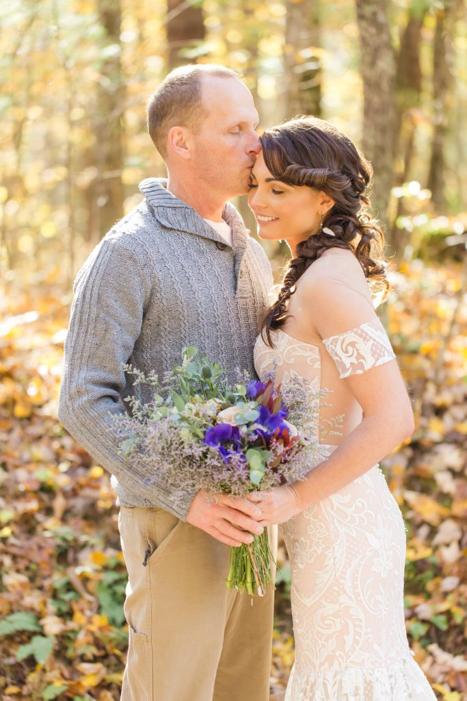 A sweet moment captured as a groom kisses his bride on the forehead in the woods.