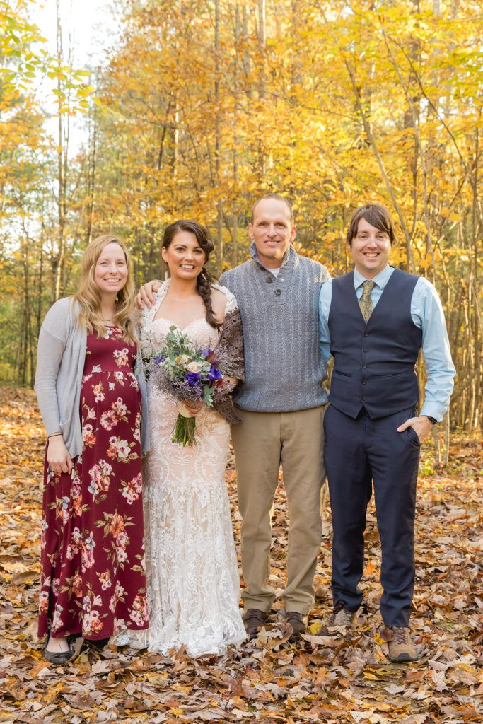 Bride and Groom with their photographers and friends in their fall forest wedding.