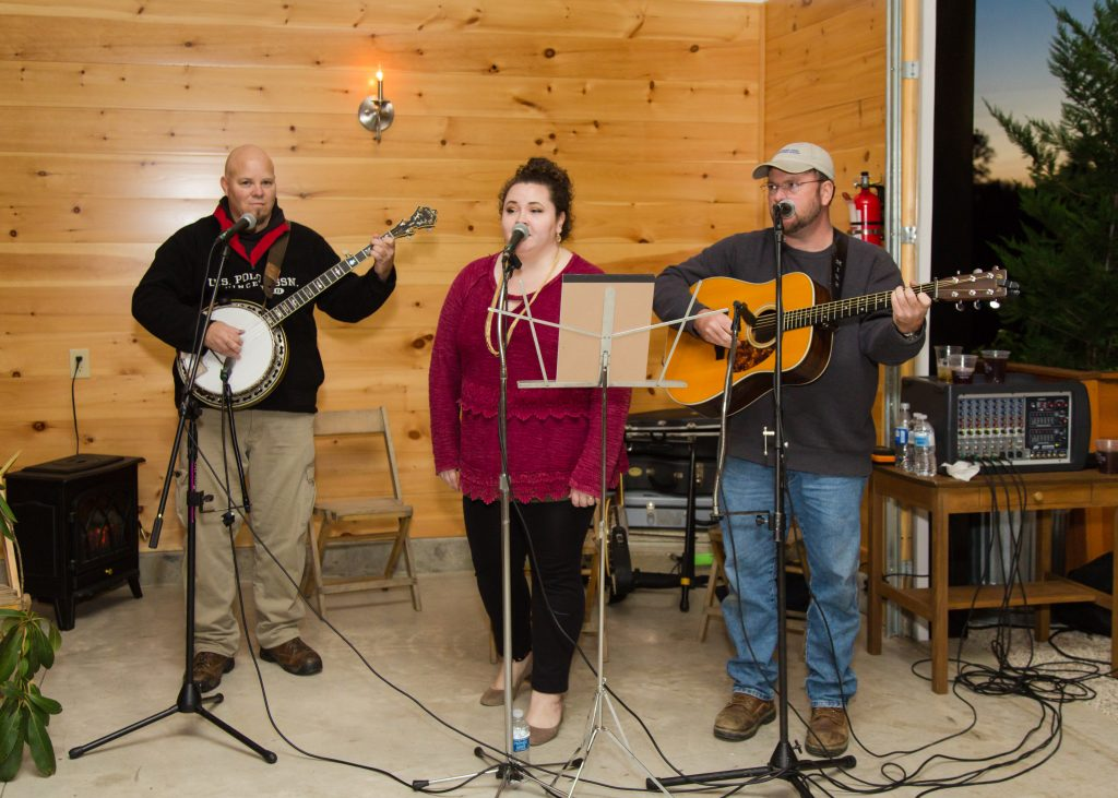 A bluegrass band plays in the reception room at Hemlock Springs as the sun sets.