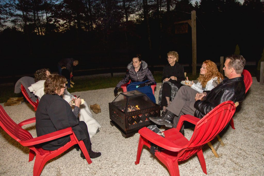 Wedding guests sit around a fire pit at a cozy fall wedding.