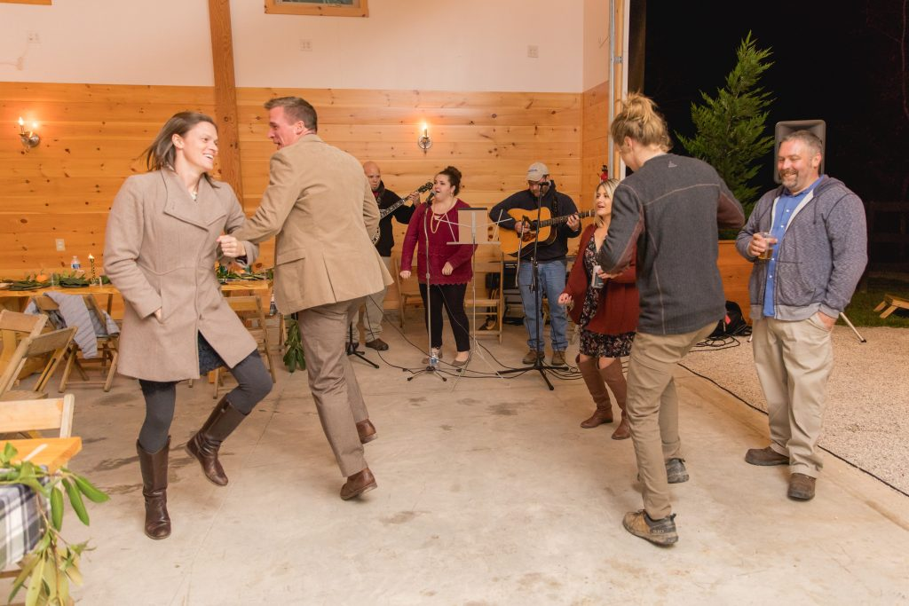 Wedding guests dance a reel as a bluegrass band plays at a cozy fall wedding in the Red River Gorge.