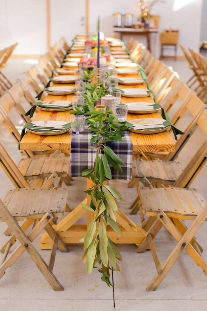 Blue and green flannel with rhododendron leaf garland graces a beautiful wood harvest table at Hemlock Springs.